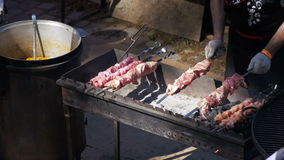 Man Preparing Barbecue on the Food Festival. Slow Motion. In 96 fps. Shish kebab from beef on skewers is cooked on Grill. Barbecue Party stock footage