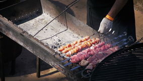 Man Preparing Barbecue on the Food Festival. Slow Motion. In 96 fps. Shish kebab from beef on skewers is cooked on Grill. Barbecue Party stock video footage