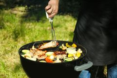Man preparing barbecue steaks with vegetables Stock Images