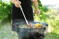 Man preparing barbecue steaks with vegetables. On grill Stock Image