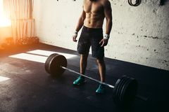 Fit man preparing for barbell training in gym. Man preparing for barbell training in gym Royalty Free Stock Image
