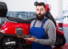 Man is preparing bill for motorcycle repair. In workshop Stock Photo