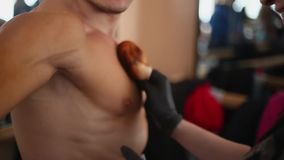 Man preparing for bodybuilding competitions. Hands spreading tan cream using a sponge on mans chest and shoulders. stock footage