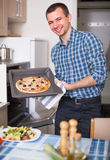 Man preparing delicious pizza in oven in kitchen at home. Young smiling man preparing delicious pizza in oven at home Stock Photography