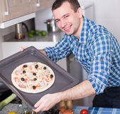 Man preparing delicious pizza in oven. Young man preparing delicious pizza in oven Stock Image