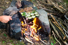 Man preparing dinner on campfire, adventure lifestyle camping vacation. Concept Stock Photos