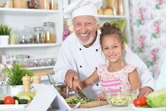 Man preparing dinner with granddaughter Stock Photography