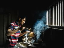 Man preparing the dishes for a festive dinner in a traditional kitchen in Kerala.