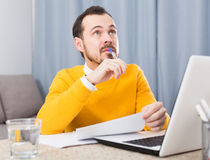 Man preparing for exams. Man in yellow shirt is preparing for exams and solve difficult tasks at home Royalty Free Stock Image
