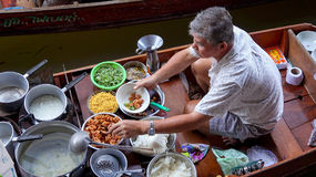 Man Preparing Food at Damnoen Saduak Floating Market Near Bangko. Man preparing food in boat at Damnoen Saduak Floating Market near Bangkok, Thailand Royalty Free Stock Image
