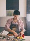 Man preparing food in kitchen stock image