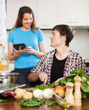 Man preparing food while woman looking at eBook Royalty Free Stock Images