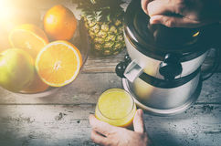 Man preparing fresh orange juice. Fruits in background Stock Photography