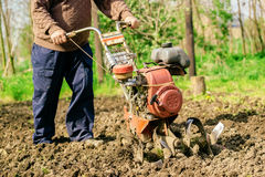 Man preparing garden soil with cultivator tiller Royalty Free Stock Photography