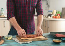 Man preparing grilled steak on the home kitchen Royalty Free Stock Images