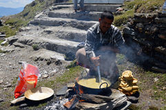 A man preparing halwa puri. Shimla, India - April 24, 2014: A man in dhoti preparing halwa poori(puri) outdoors in temple premises during tonsure&#x28 Royalty Free Stock Images