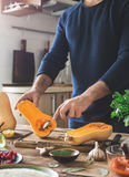 Man preparing healthy food of squash on wooden table Royalty Free Stock Photos