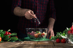 Man preparing healthy salad of fresh vegetables on wooden table. Man preparing healthy salad of fresh vegetables on a wooden table. Moody style Royalty Free Stock Photo