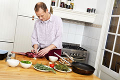 Man Preparing Meat In Kitchen Stock Photo