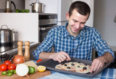 Man preparing pizza in the kitchen at home Stock Photo
