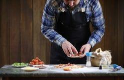 Man preparing a pizza, knead the dough and puts ingredients. A man preparing a pizza, knead the dough and puts ingredientsr Stock Image