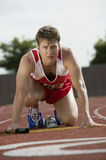 Man Preparing For Relay Race. Male athlete with baton preparing for relay race royalty free stock photo