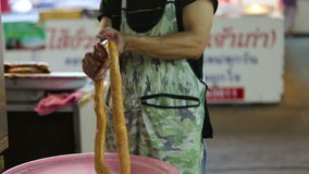 A man preparing a roll of northern Thai style sausage stock video