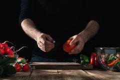 Man preparing salad of fresh vegetables in home kitchen. Cooking healthy food. Man preparing a salad of fresh vegetables on a wooden table in a home kitchen Royalty Free Stock Images