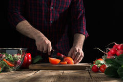 Man preparing salad with fresh vegetables on a wooden table Royalty Free Stock Image