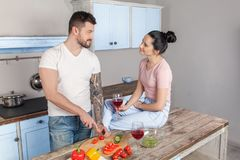 A man is preparing a salad for his beloved girl while she drinks a delicious red wine. She loves him very much royalty free stock image