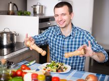 Man preparing salad in kitchen at home stock photo