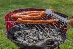 Man Preparing Sausage on Grill Stock Photography