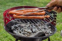 Man Preparing Sausage on Grill 2 Royalty Free Stock Photo
