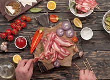 Man preparing skewers of bacon on a picnic Stock Photos