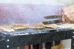 Man preparing smoky barbecue on the grill Stock Images