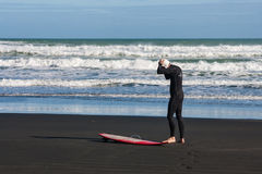Man preparing for surfing on Piha beach Royalty Free Stock Photo