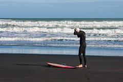 Man preparing for surfing on Piha beach Royalty Free Stock Photo