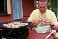 Man preparing tabletop grill stock photography
