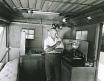 Man preparing tea inside his camping trailer Royalty Free Stock Images
