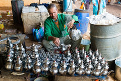 Man preparing tea with many tea pots in front of him Stock Photo