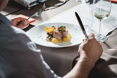 Man is preparing to eat delicious roulade of rabbit meat in a restaurant. small portion.  Royalty Free Stock Image