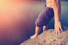 Man preparing to jump into river from high cliff Stock Images