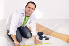 Man preparing to lay some laminate floor planks Royalty Free Stock Image