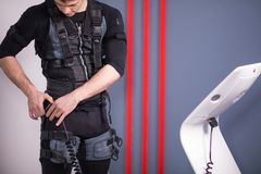Man preparing for training and connecting cables of ems suit. Handsome fit man getting prepared for ems training and wear electrostimulation suit Royalty Free Stock Photos