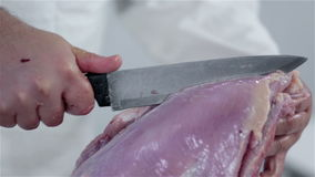 Man preparing turkey for dinner. Professional butcher preparing fresh turkey meat for cooking dishes and freezing in refrigerator for later use. Wide shots and stock video