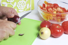 A man is preparing a vegetable salad. He cuts the onion on a cutting board. Royalty Free Stock Image