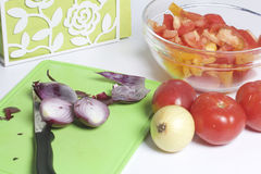 A man is preparing a vegetable salad. He cuts the onion on a cutting board. Royalty Free Stock Images