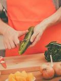 Man preparing vegetables salad peeling cucumber Royalty Free Stock Images