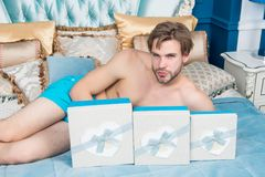 Man with present boxes lie on bed in bedroom. Boxing day concept. Valentines day, birthday, anniversary, holidays celebration. Gift giving, surprise Royalty Free Stock Photo