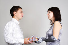 Man present gift to woman in evening dress Stock Photos